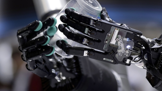 An attendant demonstrates the Tactile Telerobot system, jointly developed by Shadow Robot Company, H