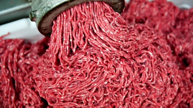 Ground beef exiting a grinder during production.