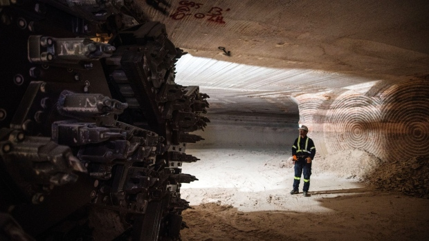 A miner stands near the cutting head of a digger near an active mining wall at the nutrien ltd cory