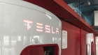 Electric vehicle charging stations stand in a Tesla Inc. Supercharger station at a parking garage in