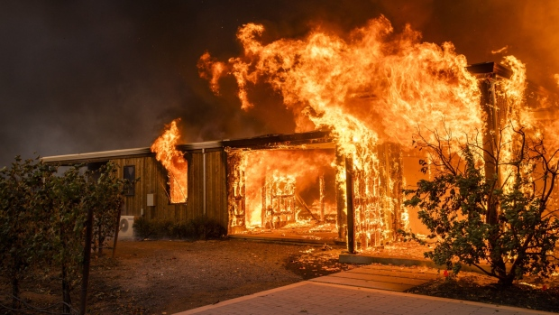 Flames engulf a home as it burns along Highway 128 during the Kincade fire in Healdsburg, California