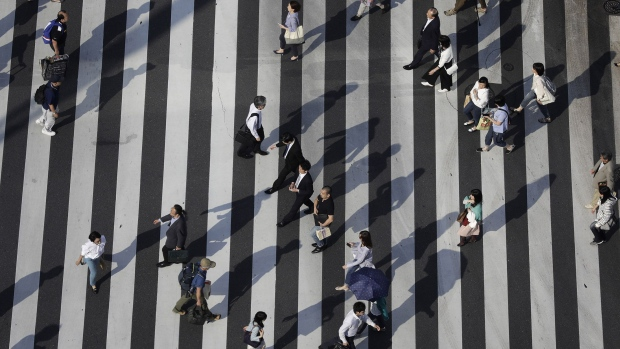 Pedestrians cross an intersection in Tokyo, Japan, on Monday, June 5, 2017. Japan\'s revised first-quarter gross domestic product (GDP) figures will be released on June 8th.