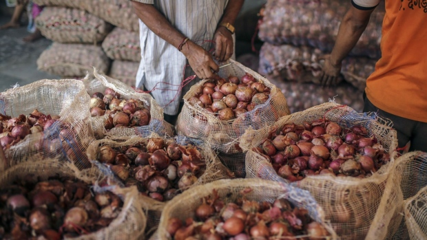 A worker seals a sack of onions at the Vashi Agricultural Produce Market Committee (APMC) wholesale market in Mumbai, India, on Thursday, Oct. 3 2019. Onions in India are once more at the epicenter of a major controversy, pitting government officials who want lower prices against farmers that need extra income.