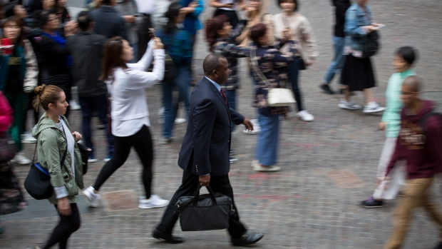 Pedestrians walk along Wall Street near the New York Stock Exchange (NYSE) in New York, U.S., on Monday, Sept. 24, 2018. U.S. stocks fell to their lows of the day after reports that Deputy Attorney General Rod Rosenstein will leave his post.