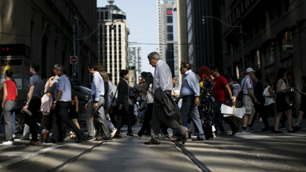 Pedestrians cross a street in the financial district of Toronto, Ontario, Canada, on Thursday, July 25, 2019. Canadian stocks fell as tech heavyweight Shopify Inc. weighed on the benchmark and investors continued to flee pot companies.