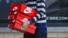 A customer carries boxes of Nike Inc. shoes outside of the NikeTown Los Angeles retail store in Beverly Hills, California, U.S., on Sunday, March 20, 2016.