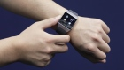 An attendant shows a Fitbit Inc. Ionic smartwatch for a photograph at the Wearable Expo in Tokyo