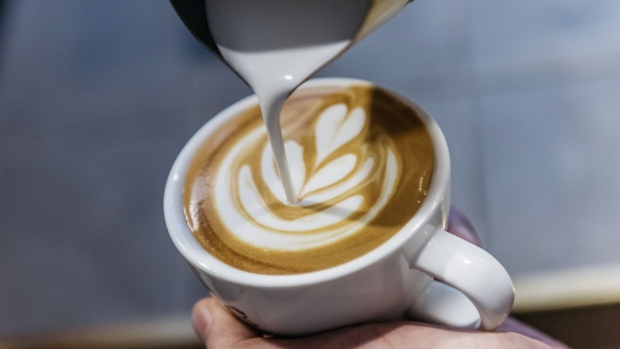 An employee pours a latte art into a cup of coffee at the Roastery Lab by Coffee Academics research and development facility, operated by Coffee Academics Group Holdings Ltd., in Hong Kong, China, on Thursday, July 27, 2017. Coffee Academics operates seven coffee outlets in Hong Kong.