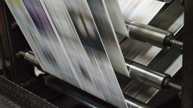 Copies of the Apple Daily newspaper, published by Next Media Ltd., move along a conveyor at the company's printing facility in the Tseung Kwan O district of Hong Kong, China, on Wednesday, June 17, 2015.
