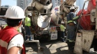 Workers pour concrete from a Cemex SAB truck at a construction site in Mexico City, Mexico