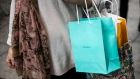 A shopper holds a bag from the Tiffany & Co. store on Fifth Avenue in New York, U.S., on Monday, Oct. 28, 2019. Tiffany & Co. may attract rival bids, analysts said, after the jewelry maker said it was reviewing an unsolicited $120 per-share bid from French luxury conglomerate LVMH.