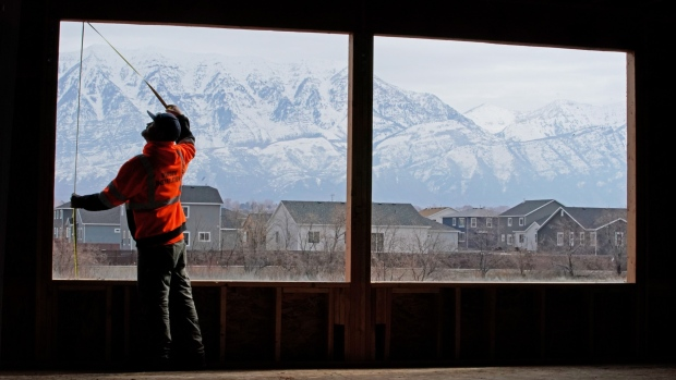 A worker measures a window opening at a home under construction in Vineyard, Utah, March 2019