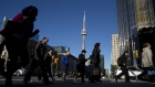 Pedestrians pass in front of the CN Tower in Toronto, Ontario, May 19, 2017. Bloomberg/Brent Lewin