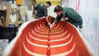 Workers apply fiberclass resin to a canoe at the Holy Cow Canoe Co. production facility in Guelph