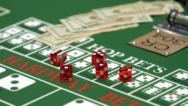 Cash and dice sit on a craps table at the Sands Casino Resort in Bethlehem, Pennsylvania, U.S., on Friday, July 16, 2010. Three casinos in Eastern Pennsylvania, including the Sands, added live game tables to their casino floors this week in an effort to attract more gamblers from New Jersey.