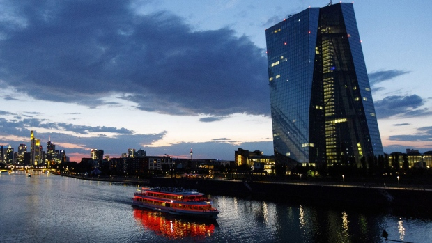 A sightseeing boat travels on the River Main past the European Central Bank (ECB) skyscraper headquarters, right, at dusk in Frankfurt.