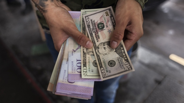 A person holds U.S. dollars and Venezuelan bolivares in Caracas.
