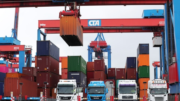 "Shipping containers are loaded onto cargo trucks, manufactured by Man SE and Scania AB, right, as Germany's Chancellor Angela Merkel, not pictured, visits the HHLA Container Terminal Altenwerder (CTA) in the port of Hamburg in Hamburg, Germany, on Monday, May 6, 2019. Merkel said Germany needs to stand up for multilateral agreements and strengthening the World Trade Organization in the face of recent ""protectionist tendencies."""