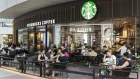 Customers sit outside a Starbucks Corp. coffee shop in Xiamen, China, on Monday, Aug. 26 2019.