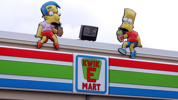 "Milhouse Van Houten and Bart Simpson props sit atop a Simpsons-styled ""Kwik-E-Mart"" 7-Eleven store"