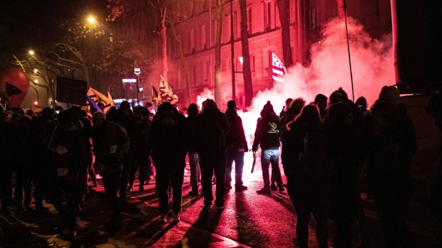 Demonstrators light a flare while protesting during a national strike in Paris on Dec. 5. Photographer: Christophe Morin/Bloomberg