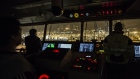 Crew members look out from the control room of CMA CGM SA's Benjamin Franklin container ship as the vessel prepares to dock at the Kwai Tsing Container Terminal in the early morning in Hong Kong, China
