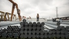 A worker stands on bundles of steel pipe stacked at a stockyard on the outskirts of Shanghai, China, on Thursday, July 5, 2018. U.S. President Donald Trump's attempts to re-balance global trade have already sent the metals world into a tizzy. As countries respond to U.S. tariffs and sanctions, the disarray is set to increase. Photgrapher: Qilai Shen/Bloomberg