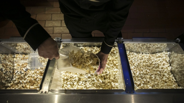 An employee scoops popcorn at a concessions stand at the Paragon Cineplex cinema.