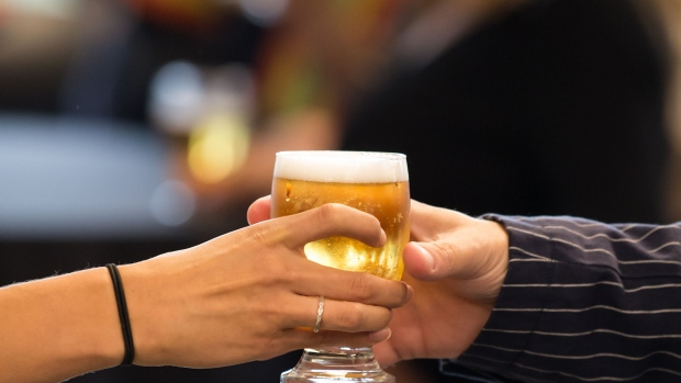 A person hands a glass of beer to a guest during a reception.