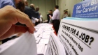 Job seekers look over job opening fliers at the WorkSource exhibitat the Pasadena Convention Center