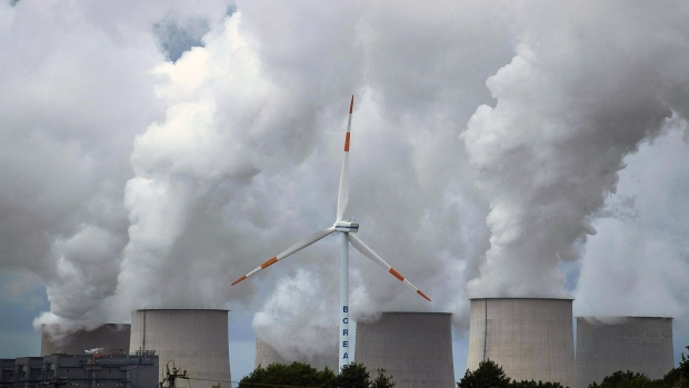 A wind turbine operates near emissions rising from the Jaenschwalde lignite fired power plant, operated by Lausitz Energie Bergbau AG (LEAG), in Barenbrueck, Germany, on Monday, Sept. 16, 2019. Policies being hammered out in Germany to slash carbon emissions may cost 40 billion euros ($44 billion) over the next four years, underscoring the wide scope of Chancellor Angela Merkels plans to boost climate protection.
