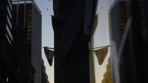 An American flag is reflected in the window of a building near the New York Stock Exchange (NYSE) in New York, U.S., on Thursday, Dec. 27, 2018. Volatility returned to U.S. markets, with stocks tumbling back toward a bear market after the biggest rally in nearly a decade evaporates.