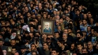 Protesters hold up an image of Qassem Soleimani
