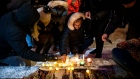 Mourners place candles and photographs during a vigil for those who were among the 176 people who we
