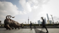Pedestrians walk past the Bund Bull statue as skyscrapers of the Pudong Lujiazui Financial District stand across the Huangpu River in Shanghai, China, on Friday, Dec. 28, 2018. China announced plans to rein in the expansion of lending by the nation's regional banks to areas beyond their home bases, the latest step policy makers have taken to defend against financial risk in the world's second-biggest economy. Photographer: Qilai Shen/Bloomberg