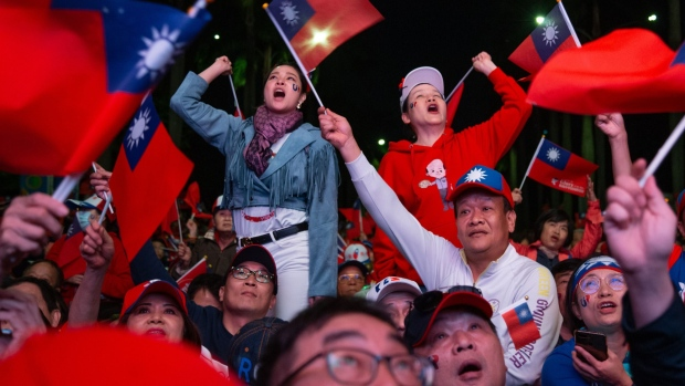 Attendees cheer while watching speeches during a Kuomintang (KMT) party campaign rally