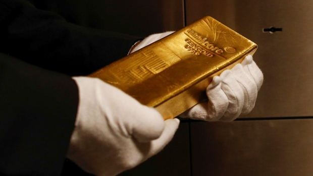 An employee holds a gold bar weighing 12.5 kilograms in the precious metals vault at Pro Aurum KG in Munich, Germany, on Wednesday, July 10, 2019. Gold rose for a third day after the Federal Reserve indicated that it's preparing to cut interest rates for the first time in a decade as the global economy slows. Photographer: Michaela Handrek-Rehle/Bloomberg