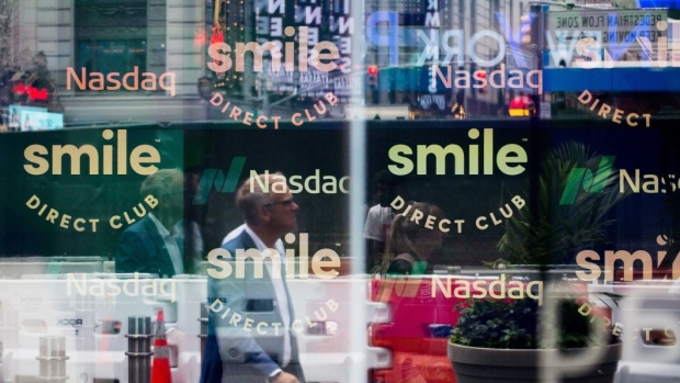 Monitors display SmileDirectClub Inc. signage as pedestrians are reflected in a window during the company's initial public offering (IPO) at the Nasdaq MarketSite in New York, U.S., on Thursday, Sept. 12, 2019. SmileDirectClub Inc. shares declined 12% from their initial public offering price in Thursday's debut. Photographer: Michael Nagle/Bloomberg