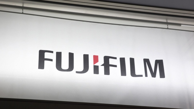 A Fujifilm logo is displayed outside the building housing headquarters of Fujifilm Holdings Corp. and Fuji Xerox Co., the joint venture between Fujifilm Holdings and Xerox Corp., in Tokyo, Japan, on Wednesday, Jan. 31, 2018. Fujifilm Holdings is gaining control of Xerox Corp. in a deal that would create an $18 billion company and see the iconic American corporate giant launching into new lines of business to seek global growth. Photographer: Tomohiro Ohsumi/Bloomberg
