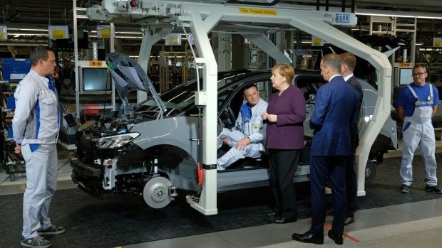 ZWICKAU, GERMANY - NOVEMBER 04: German Chancellor Angela Merkel (C) chats with workers at the assembly line of the new Volkswagen ID.3 electric car as Herbert Diess (R of Merkel), head of Volkswagen Group, looks on at the Volkswagen factory on November 04, 2019 in Zwickau, Germany. Volkswagen launched assembly of the car at the Zwickau plant today. A spokesman said the numbers of vehicles finished per day will gradually be ramped up, from a current 6 to over 50 by the end of the year, and then much higher numbers in 2020. (Photo by Sean Gallup/Getty Images)