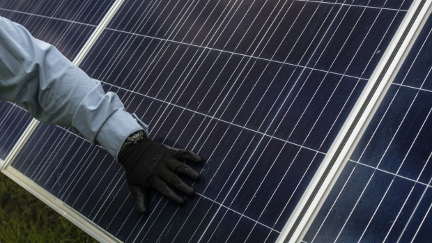 A worker inspects a solar panel at the Enel Green Power Mexico Don Jose photovoltaic solar plant in San Luis de la Paz, Guanajuato state, Mexico, on Wednesday, Aug. 14, 2019. Energy reforms begun in 2013 opened the door to private investment and specifically promoted clean energy via competitive power auctions, but new plans to strengthen state control under Mexico's President Lopez Obrador, potentially at the expense of the private sector, are forcing a change of course. Photographer: Alejandro Cegarra/Bloomberg