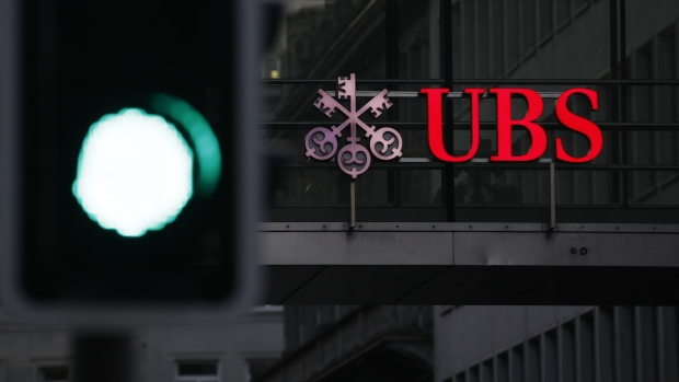 An illumiated company logo is displayed on a walkway at the UBS headquarters in Zurich, Switzerland, on Monday, Oct. 14, 2019. The spying scandal roiling Credit Suisse Group AG has also created a big headache at UBS a stone's throw away in Zurich: What to do about its star hire Iqbal Khan. Photographer: Stefan Wermuth/Bloomberg