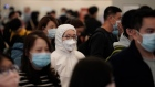 Passengers wear face masks at the departure hall of the high speed train station in Hong Kong