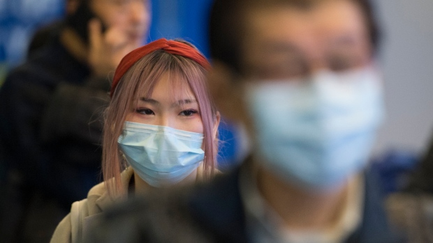 Passengers wear masks as they arrive at the international arrivals area at the Vancouver Internation