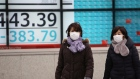 People walk by an electronic stock board of a securities firm in Tokyo, Monday, Jan. 27, 2020
