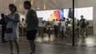Pedestrians stand outside an Apple Inc. store in Shanghai. Photographer: Qilai Shen/Bloomberg