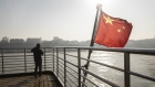 A Chinese national flag flies on the deck of a ferry crossing the Yangtze River in Wuhan, Hubei, Chi