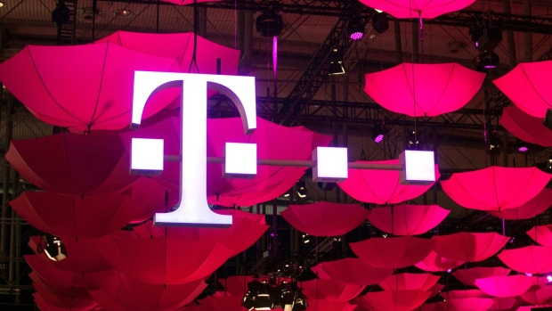 A pigeon rests on a T-Mobile logo outside a mobile phone store, operated by Deutsche Telekom AG, in Munich, Germany, on Monday, Feb. 6, 2017. Even with consumer-price growth accelerating to 1.8 percent -- a rate not recorded since early 2013 -- European Central Bank president Mario Draghi can insist that unprecedented stimulus is necessary to put the recovery on a more solid footing and stoke underlying price pressures that continue to be muted. Photographer: Krisztian Bocsi/Bloomberg