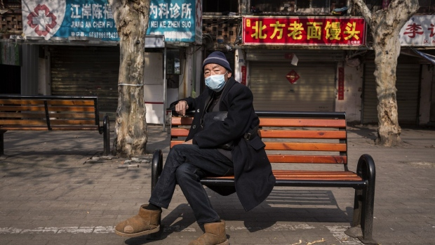 WUHAN, CHINA - FEBRUARY 05: A old woman wears a protective mask sits on a bench on February 5, 2020 in Wuhan, Hubei province, China. Flights, trains and public transport including buses, subway and ferry services have been closed for the Fourteenth day. (Photo by Getty Images) Photographer: Stringer/Getty Images AsiaPac