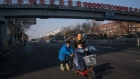 A family of three travel along an empty street in Beijing, Feb. 10.